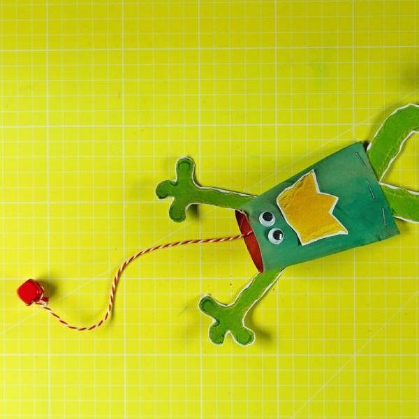 Froschfangspiel aus einer Papprolle, einem Faden, einer Perle, Wackelaugen und der ausgedruckten Bastelvorlage | Rechte: KiKA