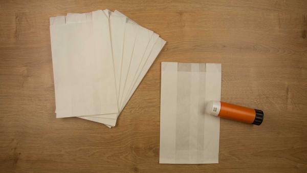 <br/>Klebe alle Butterbrottüten aufeinander: Nimm die erste Tüte. Streiche mit dem Kleber eine Linie am Boden und längs in der Tütenmitte ein. Drücke die zweite Tüte darauf. Klebe so alle Tüten zu einem Stapel zusammen. | Rechte: KiKA